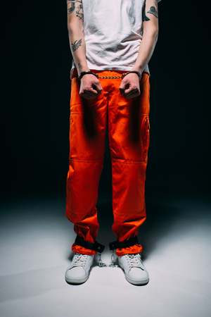 Cropped view of man wearing prison uniform with cuffs on dark background 스톡 콘텐츠