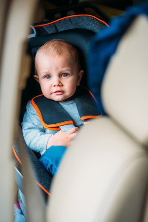 little baby sitting in child safety seat in car and looking at camera