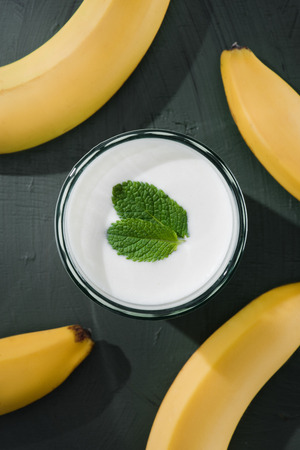top view of bananas and milkshake with mint on table 免版税图像