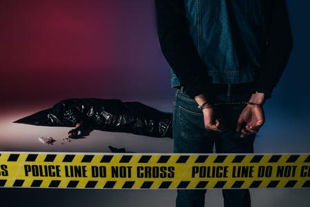 Man in cuffs by dead body behind yellow line on dark background