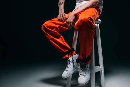 Cropped view of man in prison uniform with cuffs on legs sitting on stool on dark background