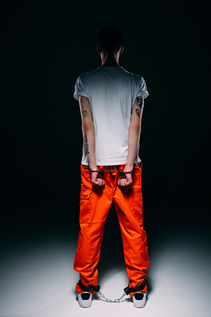 Rear view of man wearing prison uniform with hands cuffed behind his back on dark background