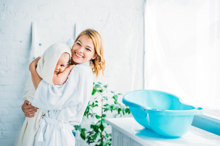 happy mother in bathrobe carrying adorable child covered in towel near plastic baby bathtub