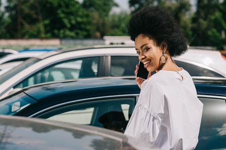 attractive african american businesswoman talking by smartphone on parking