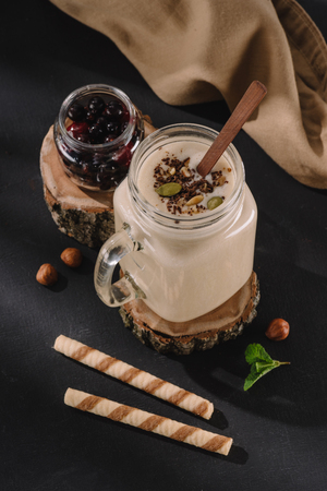 closeup view of milkshake with chocolate shavings and pistachio nuts, currants, walnuts, mint and sweet straws