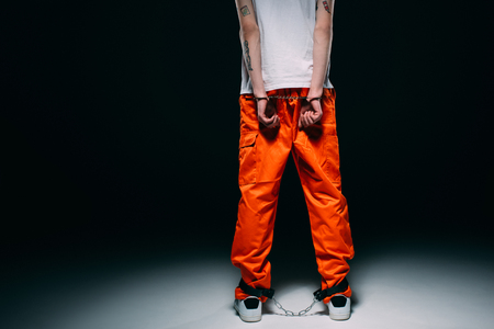 Cropped view of man wearing prison uniform with hands cuffed behind his back on dark background