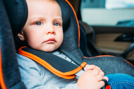 close-up portrait of thoughtful little baby sitting in child safety seat in car and looking away Stock Photo