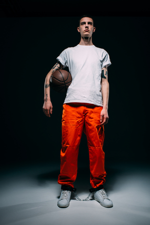 Young male prisoner wearing orange pants and cuffs holding basketball ball on dark background