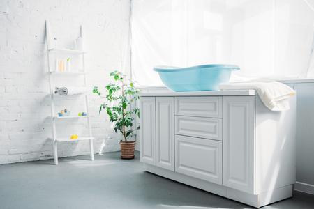blue plastic childrens bathtub on stand in white modern room
