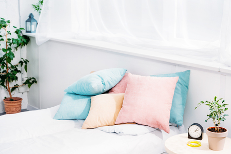 comfy bed with lot of pillows in modern light room with alarm clock and plant of bedside table Stockfoto