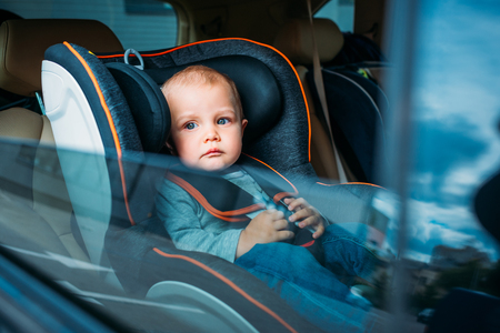 cute little baby sitting in child safety seat in car and looking through window