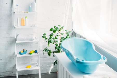 plastic childrens bathtub on stand in white modern room