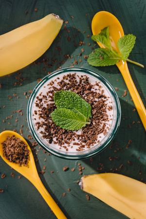 top view of milkshake with chocolate shavings and mint, spoons and bananas on table Фото со стока