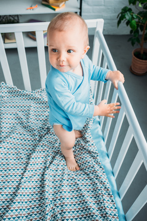 high angle view of cute little baby standing in crib