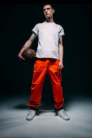 Man wearing prison uniform and cuffs holding basketball ball on dark background