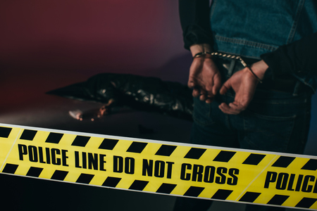 Rear view of man in cuffs by dead body behind yellow tape on dark background 스톡 콘텐츠