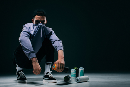 Man with covered face sitting by spray print cans on dark background Stok Fotoğraf