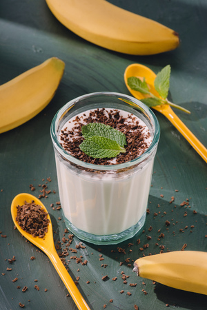closeup shot of milkshake with mint leaves and chocolate shavings, spoons and bananas