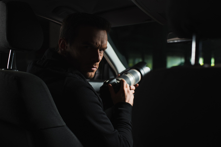 serious male paparazzi looking at camera while doing surveillance from car
