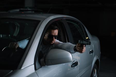 Detective privado masculino en gafas de sol que conducen por pistola de coche Foto de archivo - 106119379