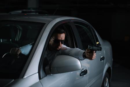 male private detective in sunglasses aiming by gun from car Reklamní fotografie
