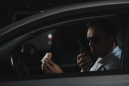 male undercover agent in sunglasses having lunch and using talkie walkie in car