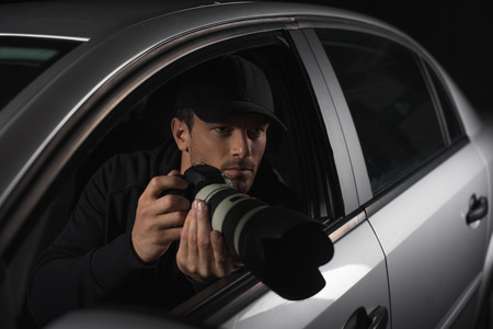male paparazzi in cap spying with camera from his car
