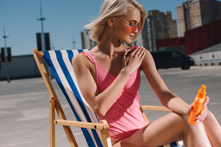 attractive young woman in pink swimsuit sitting on sun lounger and applying sunscreen lotion on parking Фото со стока