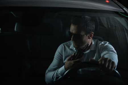 serious male undercover agent in sunglasses using talking walkie in car