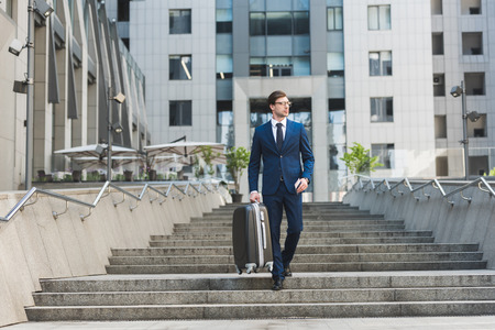 young businessman in stylish suit with luggage and flight tickets going down stairs in business district Stock Photo