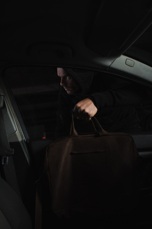 cautious male thief in black hoodie stealing bag from car Reklamní fotografie