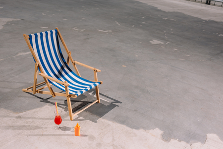 high angle view of sun lounger with cocktail and lotion on asphalt