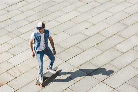high angle view of handsome young skater riding skateboard by square