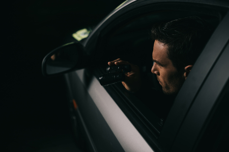 side view of male paparazzi doing surveillance by binoculars from car