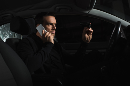 concentrated undercover male agent doing surveillance by binoculars and talking on smartphone in car Stock Photo