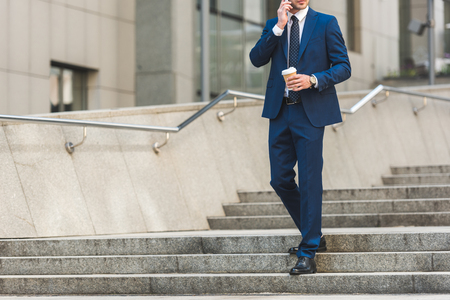 cropped shot of businessman in stylish suit with coffee to go talking by phone while walking by stairs near business building