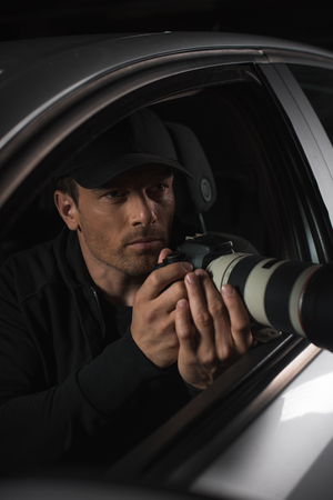 male paparazzi in cap doing surveillance by camera with object glass from his car