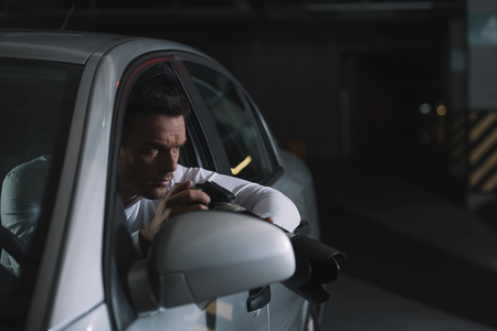 focused male private detective doing surveillance by camera from his car Stock Photo