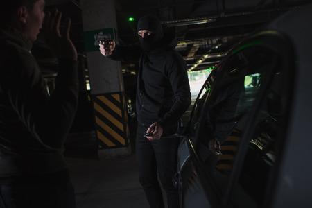 male mugger in balaclava aiming by gun on man standing near his car