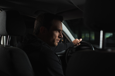 serious male private detective doing surveillance from his car Stock Photo