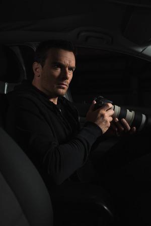 agente de sexo masculino que hace la vigilancia de la cámara por la cámara con la lente del coche Foto de archivo