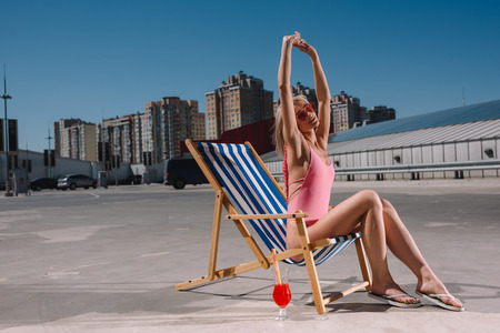 beautiful young woman stretching while relaxing in sun lounger on parking Stock Photo
