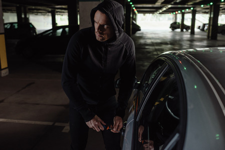cautious male robber in black hoodie intruding car by screwdriver Reklamní fotografie