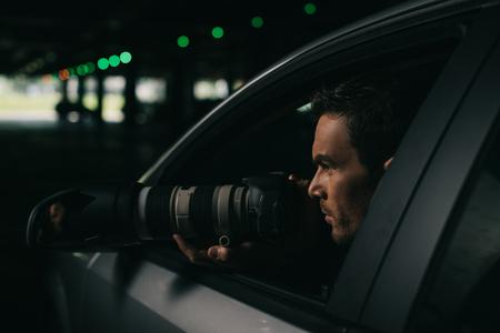 vista lateral de los hombres visagiste haciendo la vigilancia con la cámara de su coche Foto de archivo