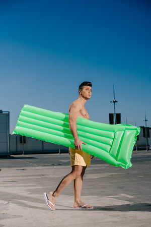 handsome young shirtless man with inflatable bed on parking