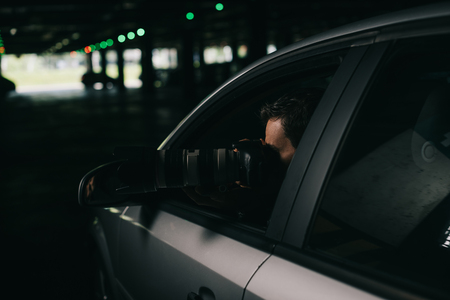 male paparazzi doing surveillance by camera with object glass from his car Stock Photo