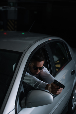 high angle view of male undercover agent in sunglasses aiming by gun from car Stock Photo