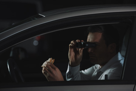 male private detective doing surveillance by binoculars and eating sandwich in car Stock Photo