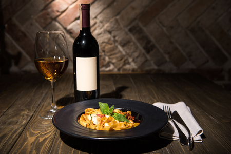 close up view of fettuccine pasta, wine and cutlery on napkin on wooden tabletop 스톡 콘텐츠