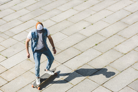high angle view of stylish young skater riding longboard by square